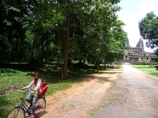 Niñas en bicicleta con el Angkor wat de fondo