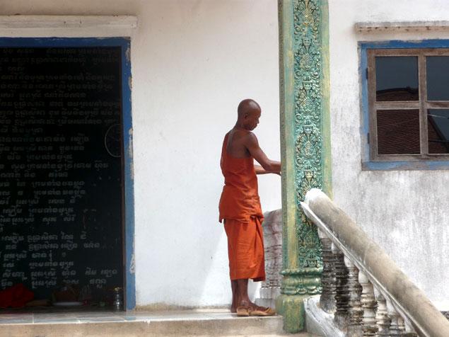 Monje en la pagoda delante del Phnom Krom