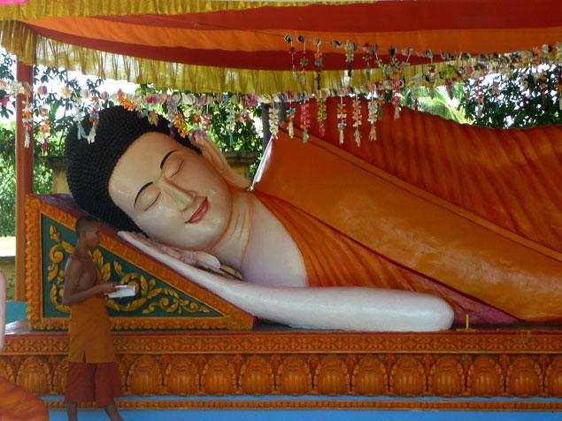 Jóven orando junto a Buda reclinado