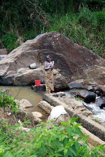 Mujer lavándose en el río