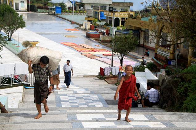 A la izquierda hombre transportando sacos vestido con Longyi