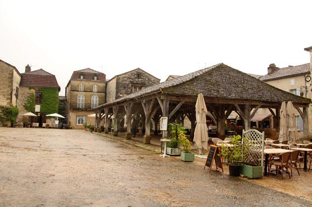 A la derecha , la estructura de madera del mercado de Monpazier
